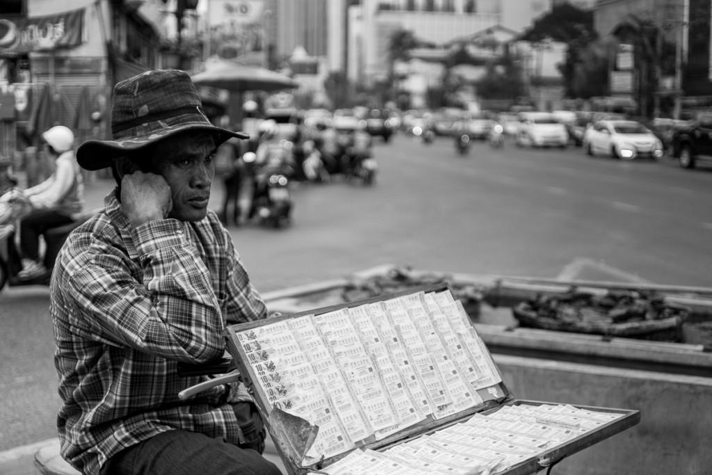 A man selling gambling tickets, waiting on a crossing. Marie Baersch, Sony a6000, Zeiss Touit 1.8/32mm.